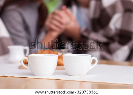 Close up of arms of man and woman holding hands with love. They are sitting in warm quilt in outdoors. There are two cups of coffee and croissants on the table. Focus on food - stock photo