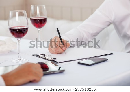Close up of arms of two business partners discussing their project. They are sitting at the table and signing a contract - stock photo