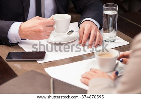 Close up of arms of two colleagues on business lunch in cafe. They are sitting at the table and drinking coffee - stock photo