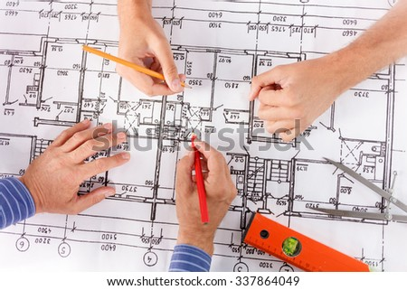 Close up of arms of two engineers drawing sketches on the blueprint - stock photo