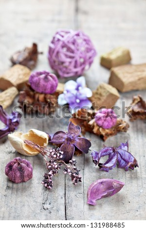 Close-up of aromatic dried flowers and other natural things on wooden surface. Potpourri used for aromatherapy. Selective focus - stock photo