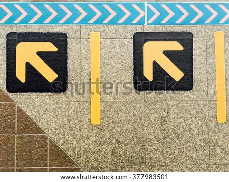 Close up of arrow sign on floor at the sky train station, bangkok, Thailand - stock photo
