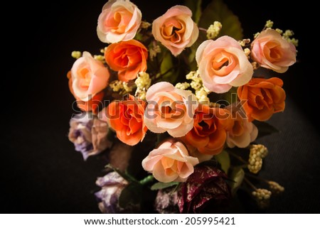 Close up of artificial flower bouquet,pink and orange rose on black. - stock photo