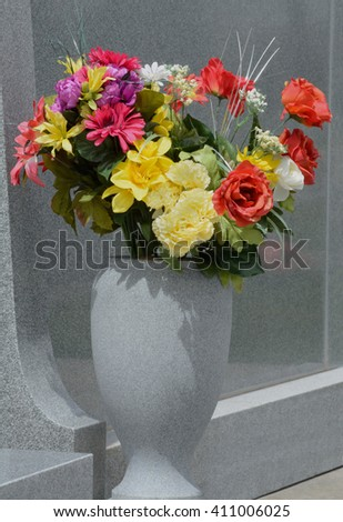 Close up of artificial flowers in vase by grave stone - stock photo