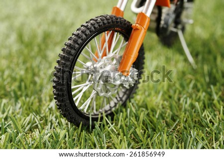 close-up of artificial green grass with motorcycle model - stock photo
