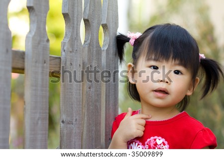Close up of Asian chinese child stands beside fence - stock photo