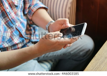 Close up of Asian man hand using mobile phone on sofa ,young adult using mobile smart phone, Internet of things lifestyle with wireless communication and internet with smart phone.