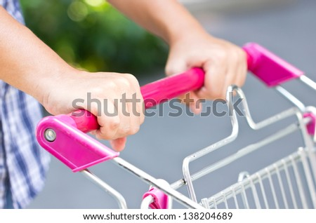 Close up of Asian man with shopping cart. - stock photo