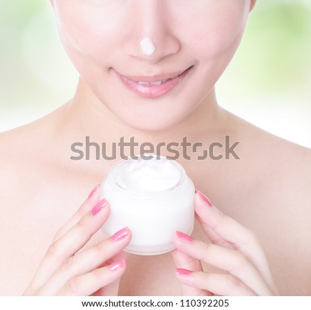 Close up of asian woman smile with moisturizer cream on face on green background - stock photo