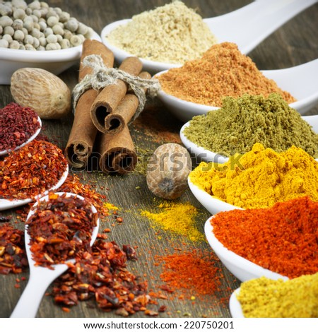 Close-up of assorted spices on wood. - stock photo