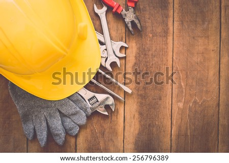 Close up of assorted work tools on wooden background