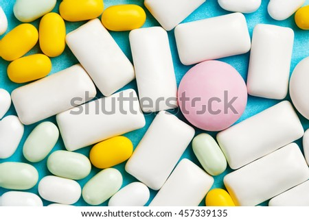 Close-up of assortment of chewing gums, mint candies and drops on bright blue background - stock photo