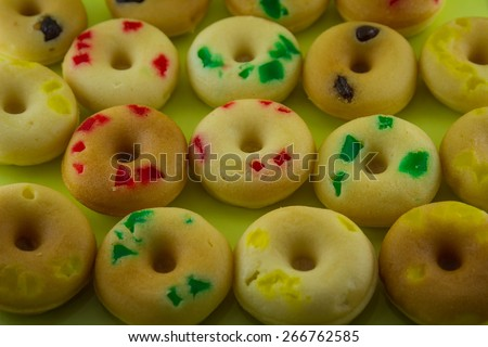 Close up of assortment of homemade vanilla bean donuts with colorful icing sitting on metal baking pan - stock photo