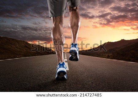 Close up of athlete's legs running on the empty road at the sunset - stock photo