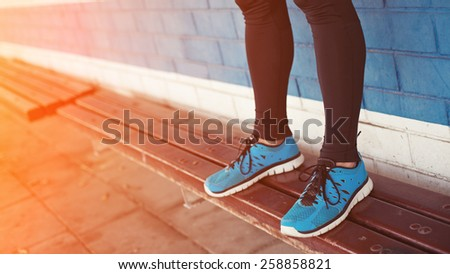 close-up of athlete's legs with running shoes (intentional sun glare) - stock photo