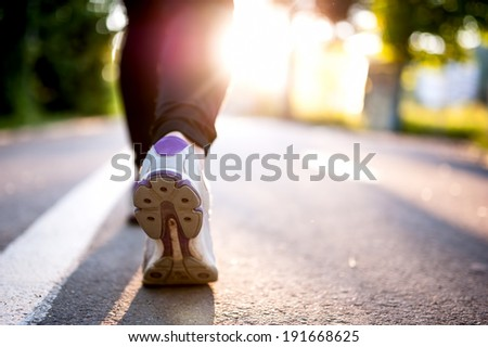 Close-up of Athlete shoes while running in park. Fitness concept with female athlete jogging in city park - stock photo