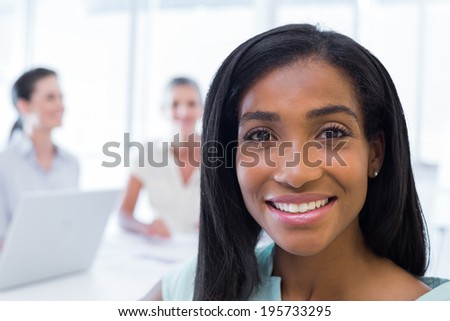 Close up of attractive businesswoman smiling while her coworkers are working behind her - stock photo