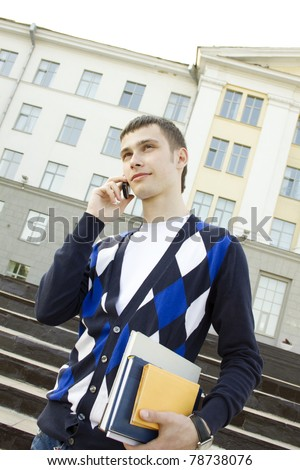 Close-up of attractive male students on campus talking on the phone - stock photo