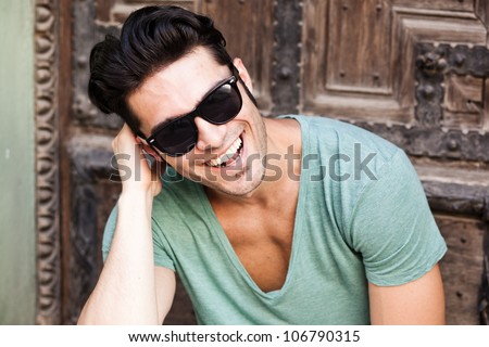 close-up of attractive man smiling wearing sunglasses - stock photo