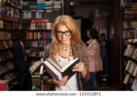close-up of attractive young girl with geeky eyeglasses in bookshop reading something from a book and laughing, ith other people and booksheles in background - stock photo
