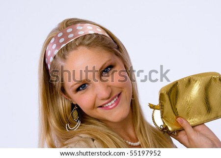 Close up of attractive young woman holding a gold purse and smiling at camera. - stock photo