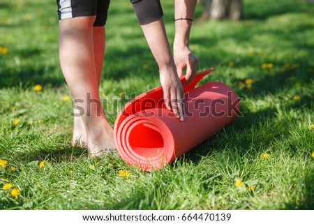 Close-up of attractive young woman unfolding red yoga or fitness mat before working out outdoors on the grass.
