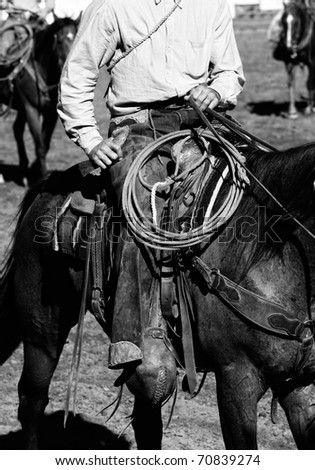 Close-up of authentic cowboy in the American West preparing to work inside an arena with other cowboys in the background (shallow depth of field, black and white). - stock photo