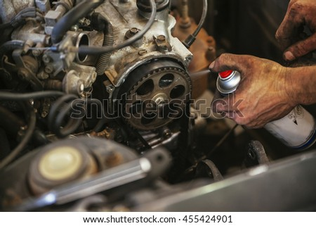 Close Up Of Auto Mechanic Hands Spraying Fluid For Greasiness