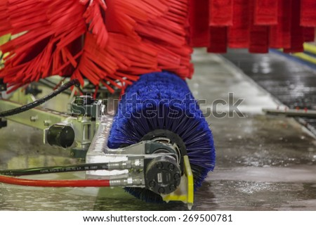 Close up of automatic car wash red and blue brushes in action - stock photo