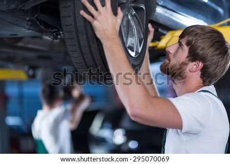 Close-up of automobile mechanics repairing a car - stock photo