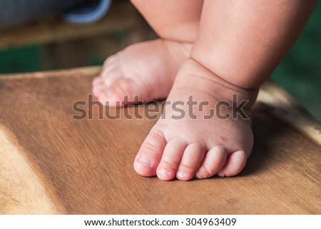 Close up of baby feet on wooden background - stock photo