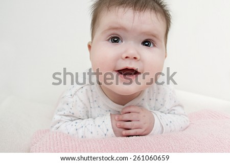 Close up of baby girl laying on her tummy happily smiling - stock photo