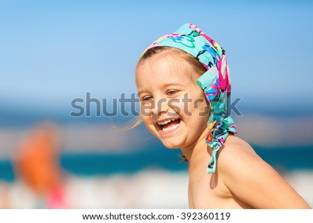 Close-up of baby girl with a bandanna on his head on a blurred background of blue sky and sea. Laughing happy child. Hot sunny summer day. Selective focus. - stock photo