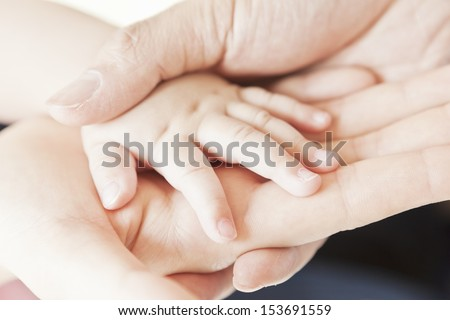 Close-up of baby hand into parents hand