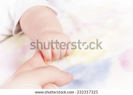 Close up of baby's hand touching mother's finger - stock photo
