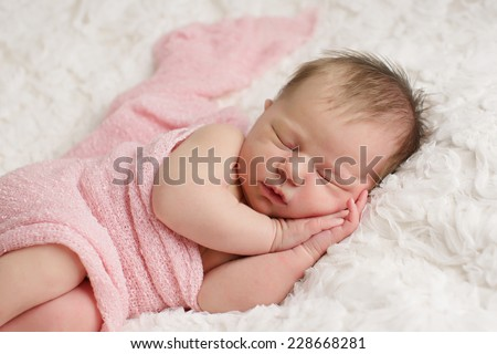Close up of baby wrapped in pink sleeping with hands under her face
