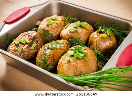 close up of baked potatoes with green onion in oven tray - stock photo