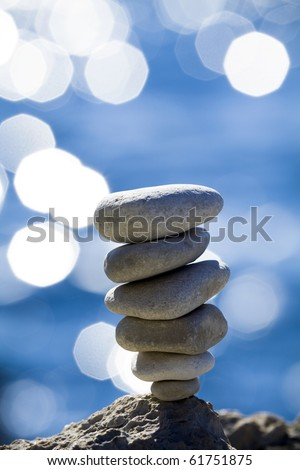 Close-up of balanced pebbles stack over blue sea - stock photo