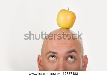 Close-up of bald male head with yellow apple on it - stock photo