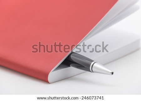 Close up of ballpoint pen with red leather notebook or organizer for writing down ideas and business plan - stock photo