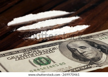 close-up of banknote and white powder on a wooden table, studio - stock photo