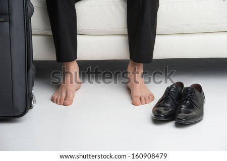 Close up of bare feet of a business man. Having traveling suitcase and shoes near  - stock photo