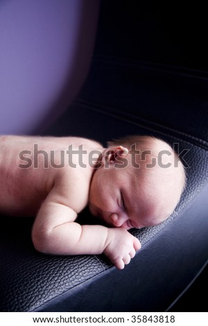 Close-up of bare newborn baby lying on chair