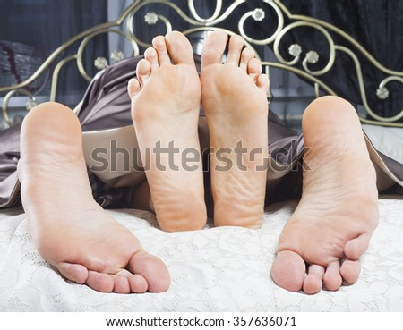 Close up of barefoot couple in bed  - stock photo