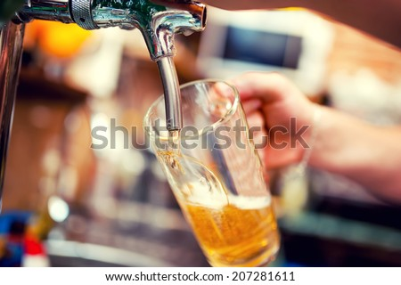 close-up of barman hand at beer tap pouring a draught lager beer - stock photo