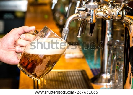 Close-up of bartender hand at beer tap pouring a draught lager beer - stock photo
