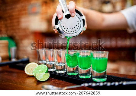 Close-up of bartender hand pouring alcoholic drink in restaurant, pub or bar - stock photo