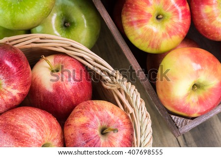 Close up of basket and crate with assorted ripe apples on a wooden background. - stock photo