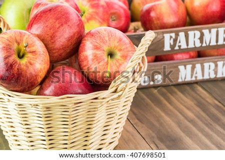 Close up of basket with ripe apples with farmers crate in the background. - stock photo