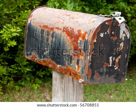 Close up of battered and rusty black mailbox along a rural road. - stock photo